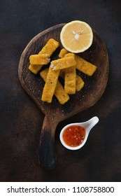 Roasted fish fingers with lemon and sauce on a rustic wooden serving board, flatlay over dark brown metal background, vertical shot