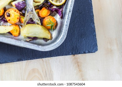 Roasted fish tale on baking tray with vegetables