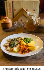 Roasted fish with vegetables meal in restaurant on wooden table