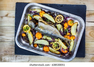Roasted fish with veggies on granite board