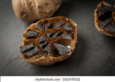 Roasted garlic cloves over black and copy space