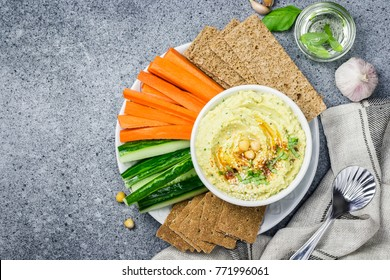 Roasted garlic hummus in a bowl and vegetable sticks on stone or concrete background. Top view,space for text.