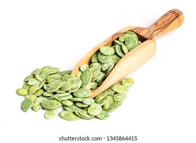 Roasted green tea pumpkin seeds on wooden scoop