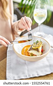 Roasted Halibut with vegetables, paprika pepper and pumpkin cream. Lunch in a restaurant, a woman eats delicious and healthy food. Dish decorated with a slice of lemon. Restaurant menu