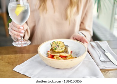 Roasted Halibut with vegetables, paprika pepper and pumpkin cream. Lunch in a restaurant, a woman eats delicious and healthy food. Dish decorated with a slice of lemon. Restaurant menu.