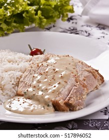Roasted ham with mustard sauce, served with rice and salad