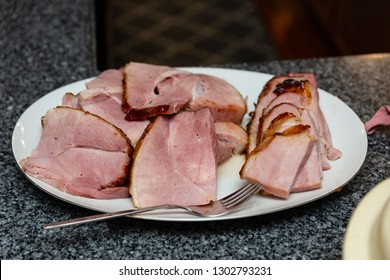 a roasted ham on a white platter all ready for serving