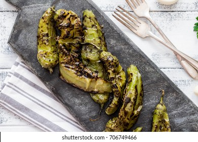 Roasted hatch chili peppers on the cutting board. Fall harvest. Summer menu. Rustic style. Vegetarian menu. Green chilies. Hatch Chile Festival.