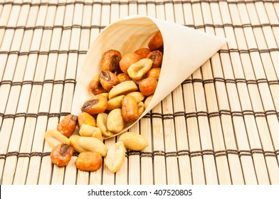 Roasted hazelnuts in a cone on wooden mat
