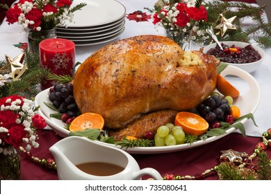 Roasted herb rubbed turkey garnished with fresh grapes, oranges, and cranberry is ready for Christmas dinner. Ornaments, Champagne, candles, and other Christmas decorations on feast table.