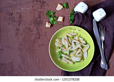 Roasted Jerusalem artichoke with cheese and parsley on a green plate. Top view, copy space. Healthy food
