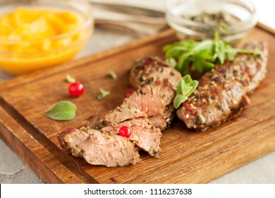Roasted lamb fillet with spicy crust, cranberries and sage leaves on wooden cutting board