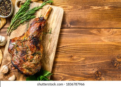 Roasted lamb, sheep leg on a cutting board with rosemary. wooden background. Top view. Copy space