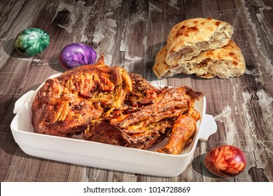 Roasted Lamb Shoulder Served With Leavened Flatbread And Colorful Easter Eggs On Old Lacquered Cracked Flaky Garden Table