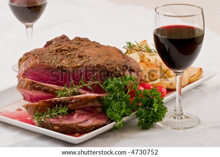 Roasted leg of lamb with roasted potatoes and glass of wine