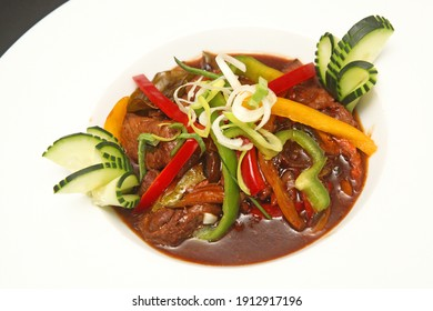 Roasted liver with sauce, lettuce and cucumber on dish in the restaurant
