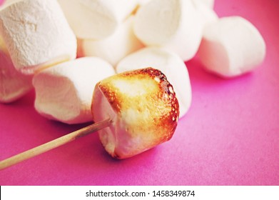 Roasted marshmallow on stick before white ones at pink background.