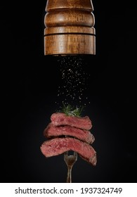 Roasted meat. Milled spices falling from pepper mill on grilled pieces of beef steak medium rare on fork on black background. Steak menu. Grilled menu.