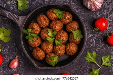 Roasted  meatballs with tomatoes, garlic and parsley. Top view, copy space.