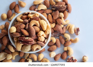 roasted mixed nuts in white ceramic bowl on barble table background.