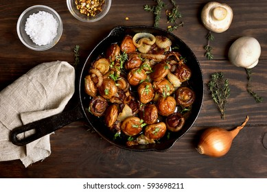 Roasted mushrooms with onion in frying pan over wooden background, top view