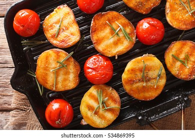 roasted new potatoes and tomatoes with rosemary closeup on a grill pan. Horizontal view from above