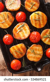 roasted new potatoes and tomatoes with rosemary close up on a grill pan. vertical view from above