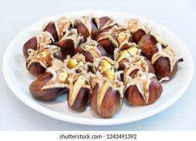 roasted open edible chestnuts served on white dish, tasty food