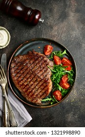 Roasted organic rancho beef steak with vegetables salad and garlic sauce on a plate over dark slate, stone, metal or concrete background.Top view with copy space.