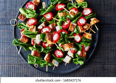 Roasted with paprika chicken, peppers stuffed with cream cheese,  and spinach on skewers on a black plate on a dark wooden table, horizontal view, close-up, top view