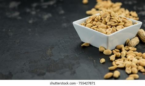 Roasted Peanuts on a vintage slate slab (selective focus; close-up shot)