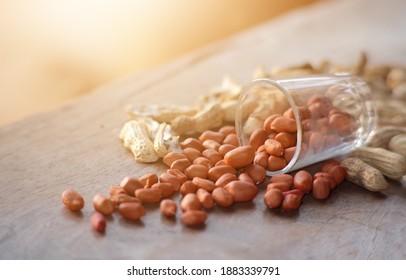Roasted peanuts on wood table with light.