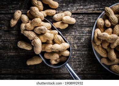 Roasted peanuts. Tasty groundnuts in metal scoop on wooden table. Top view.