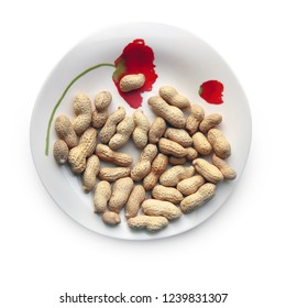 Roasted peanuts in their nutshells on the beautiful plate against white background. Selective and soft focus.