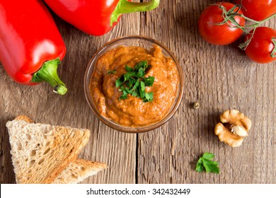 roasted pepper dip with nuts and bread in glass bowl over rustic wooden background closeup