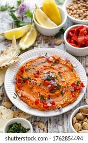 Hummus au poivre rôti saupoudré de persil haché et de fleurs de frites comestibles, vue de dessus