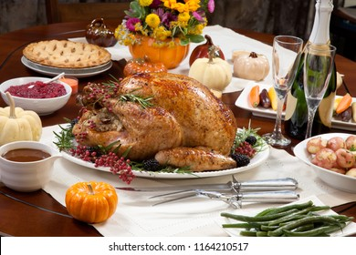 Roasted pepper turkey for Thanksgiving, garnished with pink pepper, blackberry, and fresh rosemary twigs on a dinner table decorated with mini pumpkins, beans, candles, and flutes of champagne.