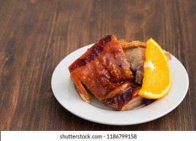 roasted piglet with orange on white plate