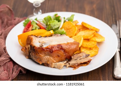 roasted piglet with potato chips and orange on white plate