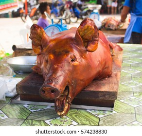 Roasted pig's head on market's table in sunlight. Tasty meat lunch photo. Whole pork grilled. Traditional Philippines dish. Pinoy lechon image. Outdoor eatery food. Meat delicatessen - grilled pork