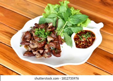 Roasted pork Chitterlings with chilli sauce spicy in a white plate on a wooden tableor Grilled pork intestine local street food of Thai spicy eat with sticky rice papaya salad som tum lab moo.