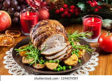 Roasted pork ham served with baked potatoes. Concepts of holiday food.