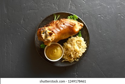 Roasted pork knuckle with braised cabbage (sauerkraut) and mustard on black stone background with copy space. Top view, flat lay