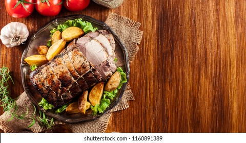 Roasted pork loin with baked potatoes and herbs on a plate
