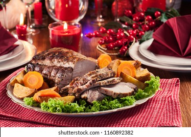 Roasted pork loin with baked potatoes and vegetables. Christmas atmosphere