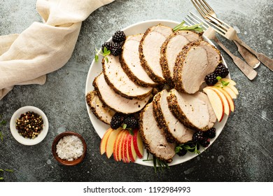 Roasted pork loin with dry rub sliced on a plate overhead view