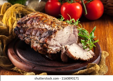 Roasted pork loin with herbs on cutting board