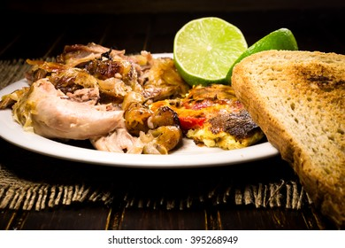 Roasted pork meat, limes and scrambled eggs with red papers and slices of bread