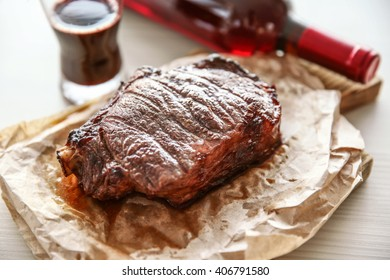 Roasted pork steak with bottle of red wine on light wooden background