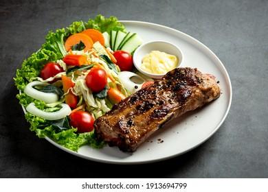 Roasted pork steak and vegetables on plate.